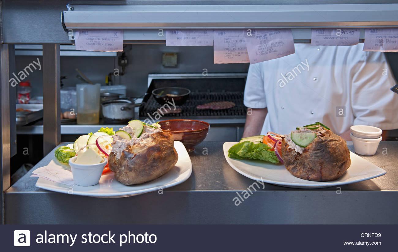 Teller mit Essen im Restaurantküche Stockbild