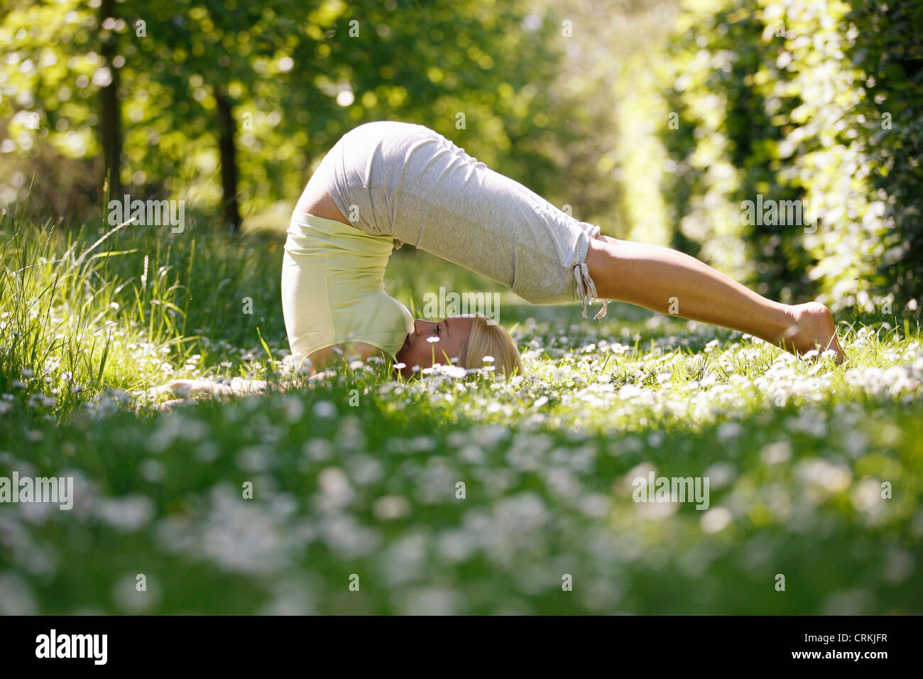 Eine junge Frau praktizieren Yoga außerhalb Pflug-pose Stockbild