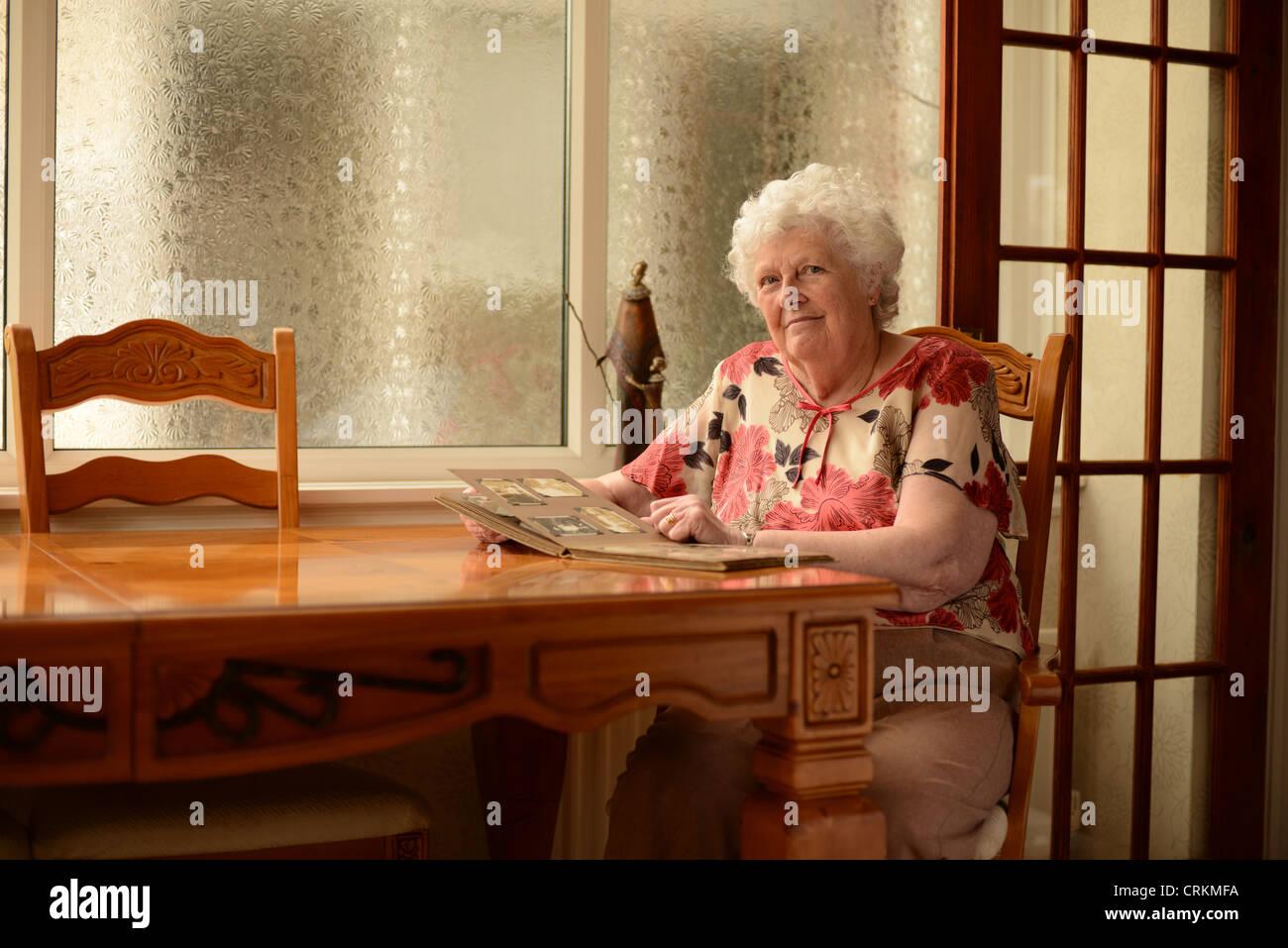 Eine ältere Dame, die Fotos in einem Album betrachten saß am Tisch Stockbild