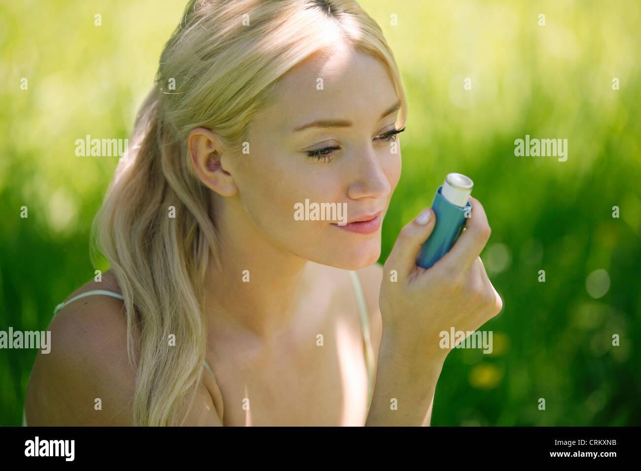 Eine junge, blonde Frau sitzen auf der Wiese mit einem Asthma-Inhalator Stockbild