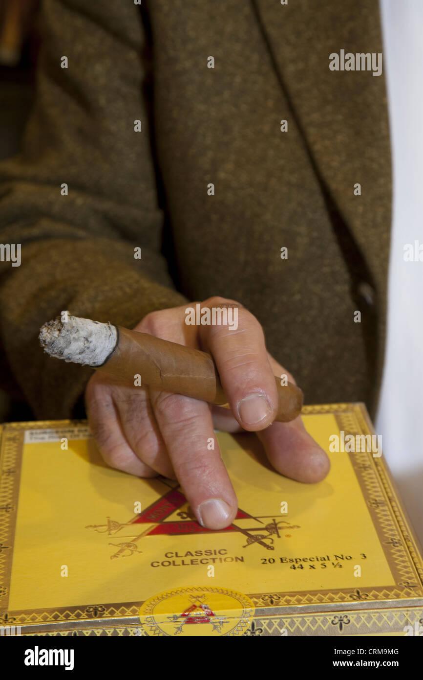 Bild der Hände halten brennende Zigarre beschnitten Stockbild