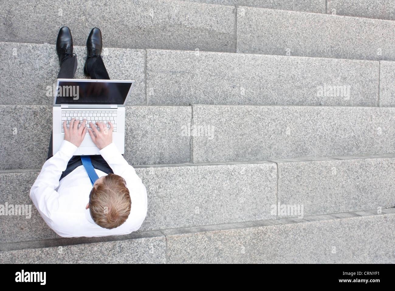 Business-Mann sitzt auf der Treppe im freien Stockbild