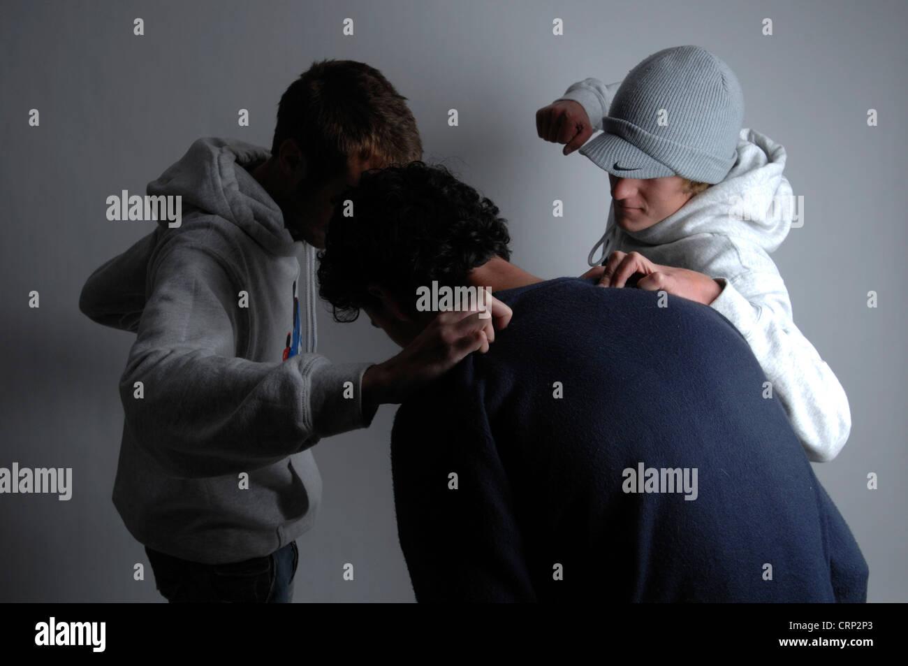 Zwei junge Männer verprügeln eines jungen Mannes Stockbild