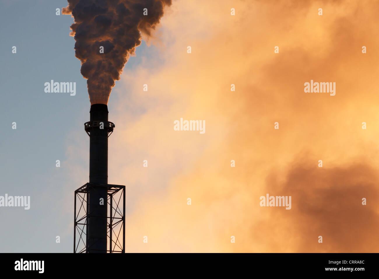 Ein Schornstein Rauch in einer frühen Morgenhimmel gießen. Stockbild