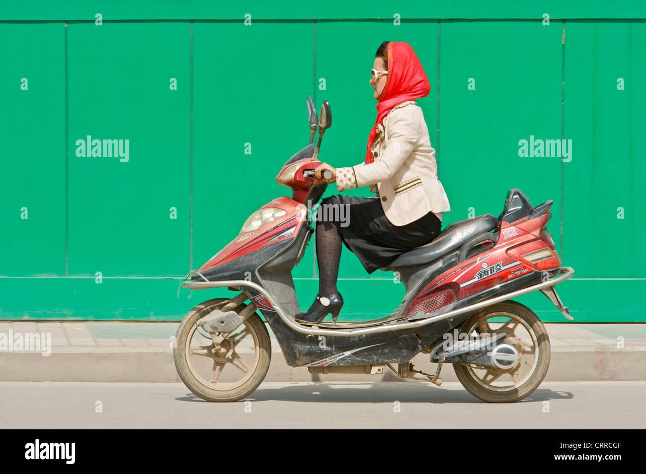 Eine chinesische Frau reist entlang einer Straße auf ihrem Roller in Kashgar. Stockbild
