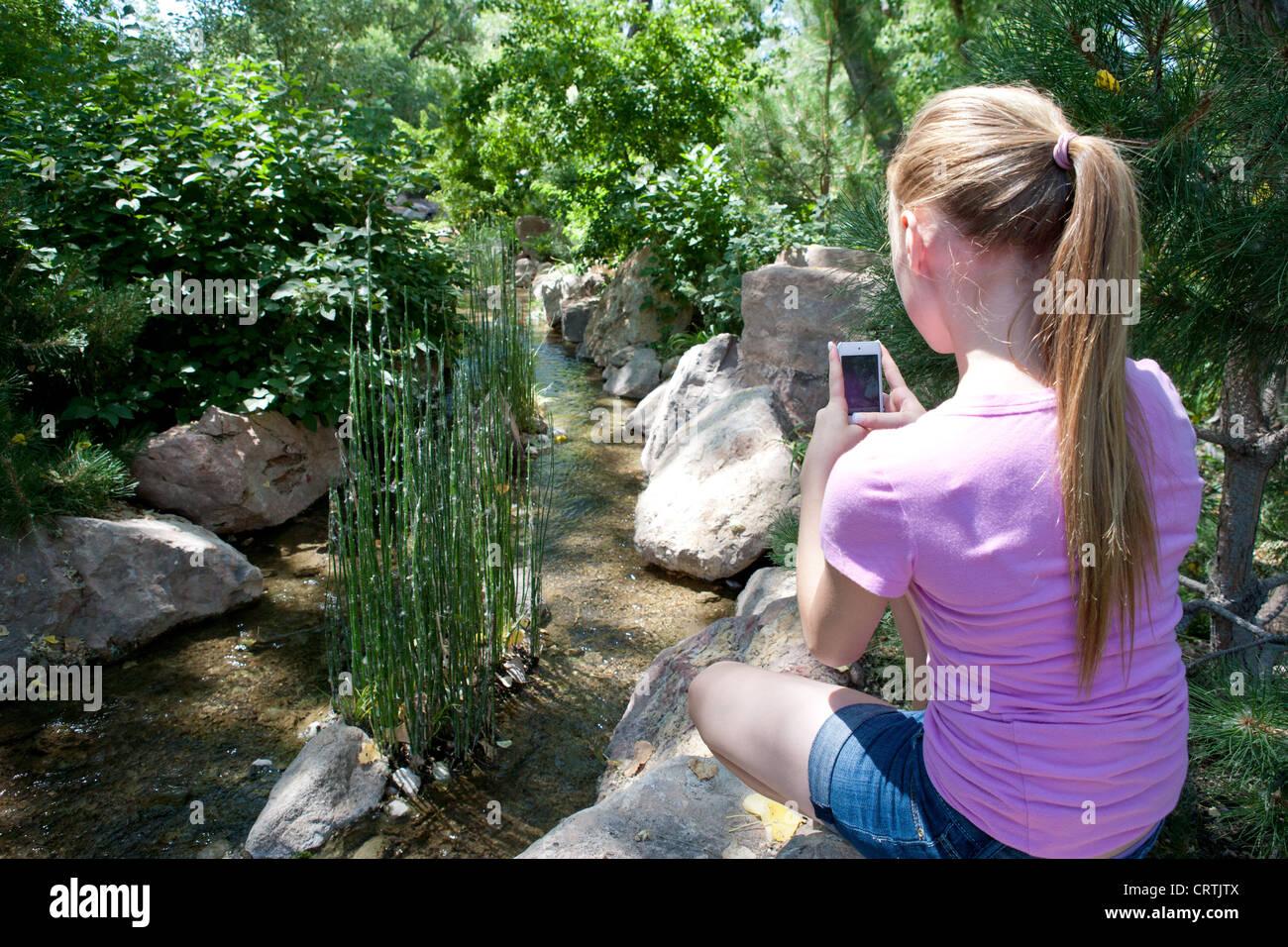 13 Jahre altes Mädchen nimmt ein Bild von einem Teich mit ihrer Iphone-Kamera. Stockbild