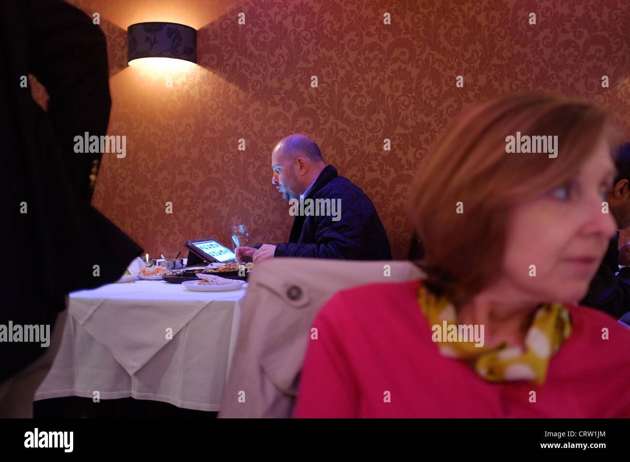 Ein Mann allein mit einem Tablet-Computer in einem indischen Restaurant Essen Stockbild