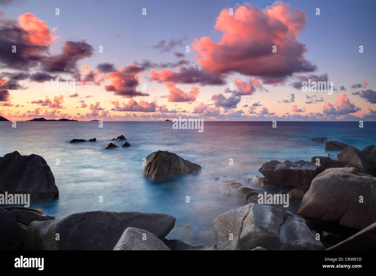 Wolken über der Baie Ste Anne bei Sonnenuntergang vom Nordende von La Digue auf den Seychellen gesehen Stockbild