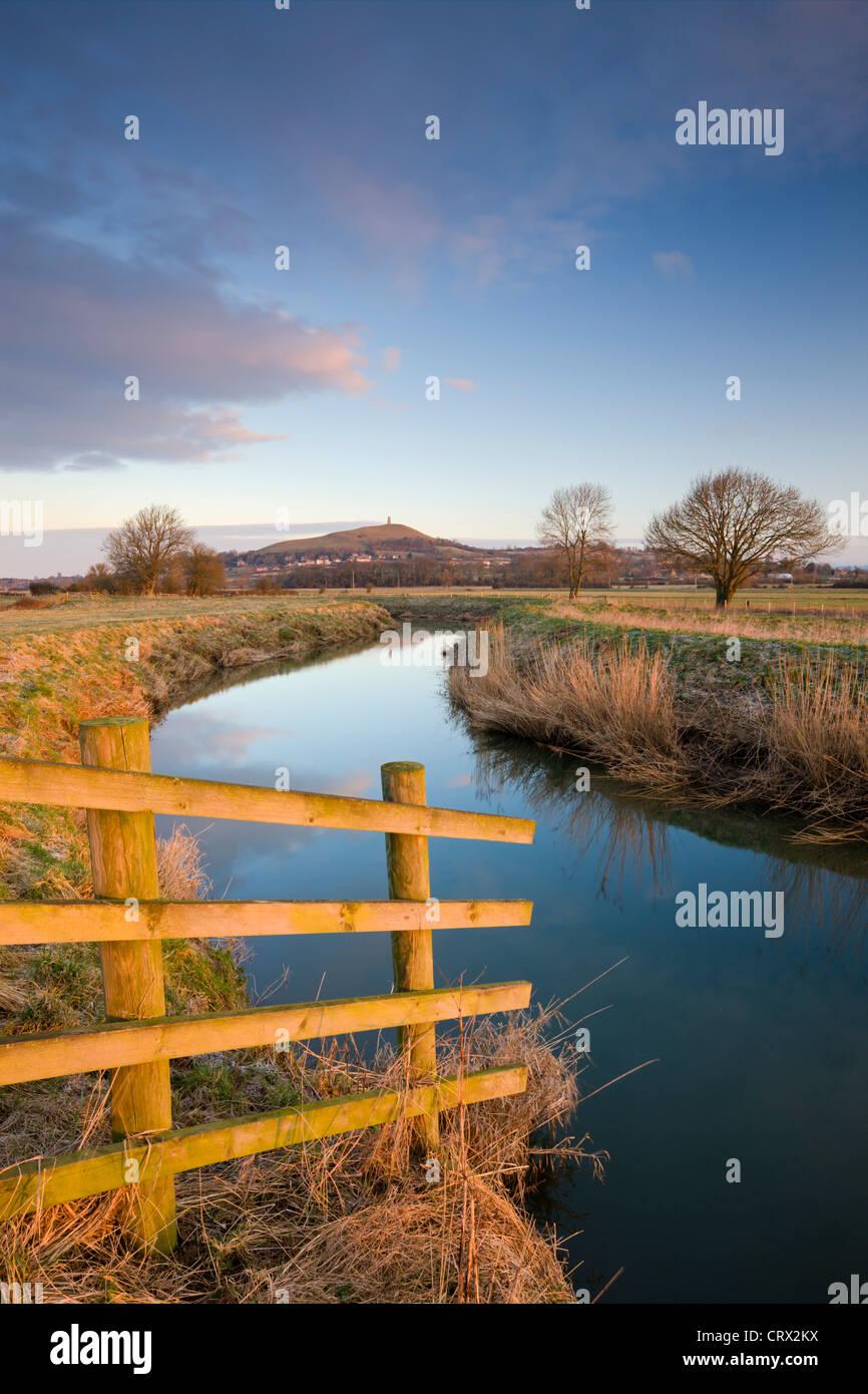 Ersten Licht des morgens am Glastonbury Tor gesehen vom Fluß Brue, Somerset Levels, Glastonbury, Somerset, Stockbild