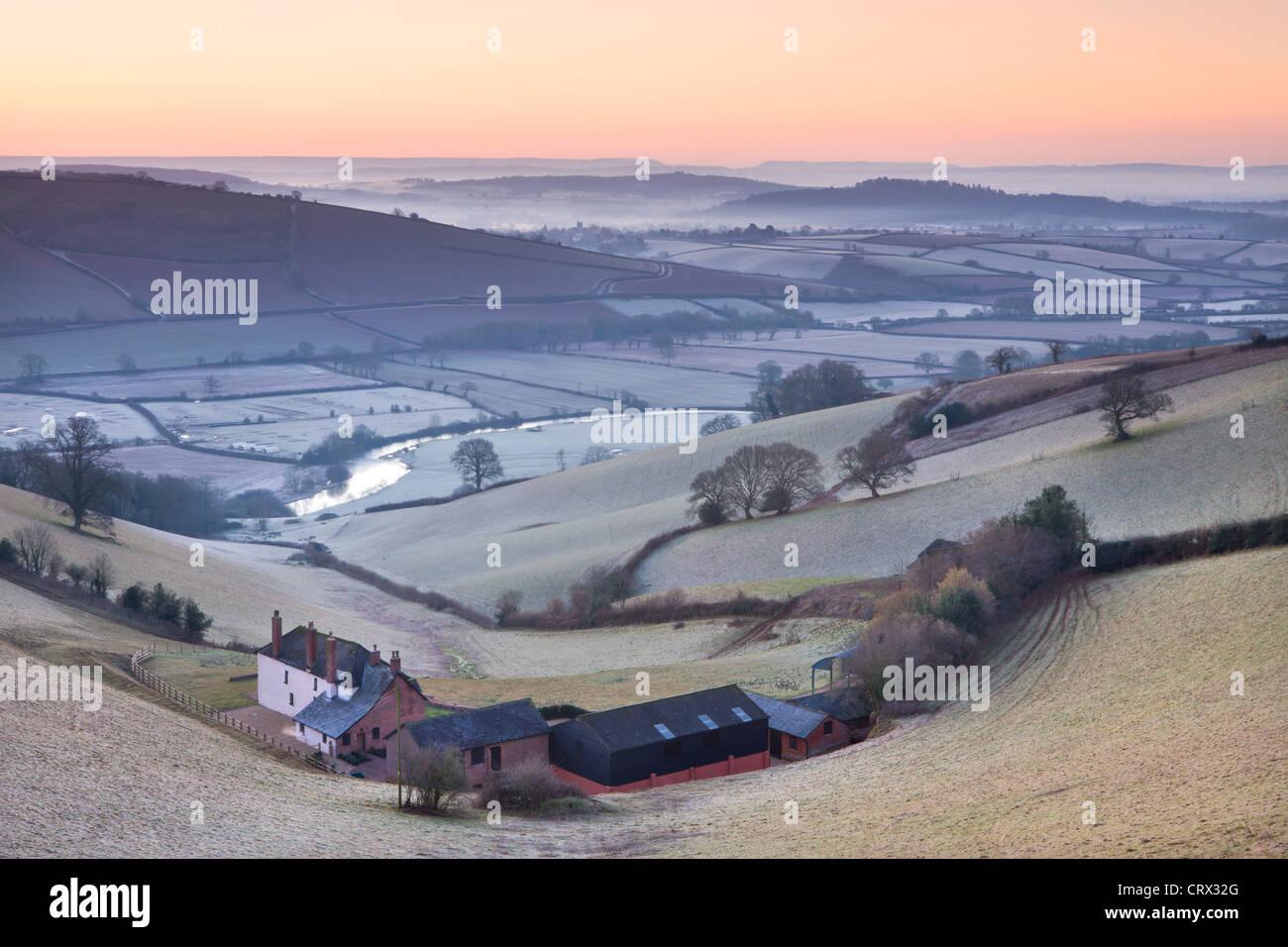 Frost überzogen Landschaft und landwirtschaftlichen Gebäuden bei Sonnenaufgang, Exe Valley, Devon, England. Stockbild