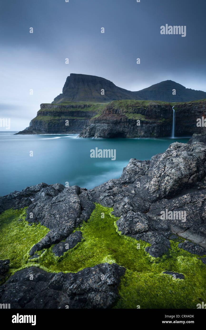 Dramatische Küstenlinie und Wasserfall am Gasadalur auf der Insel Vagar, Färöer. (Juni) Frühjahr Stockbild
