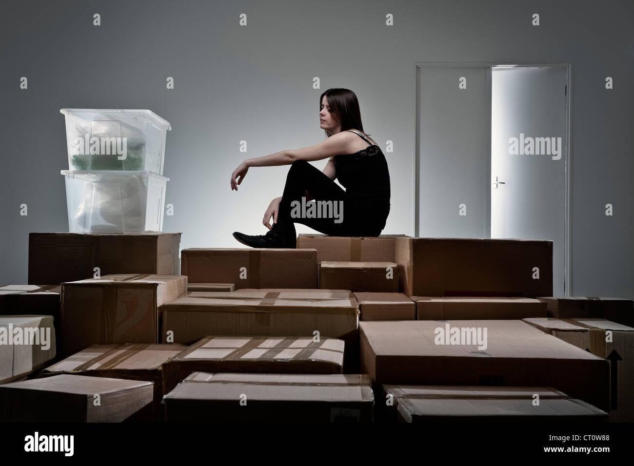 Teenager-Mädchen sitzen auf Kartons Stockfoto