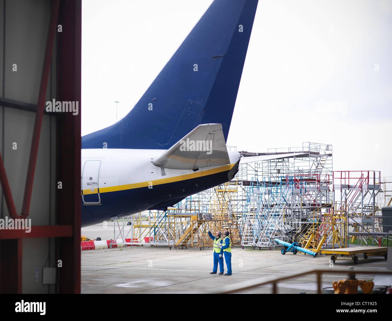 Arbeitnehmer, die Unterseite des Flugzeuges zu prüfen Stockbild