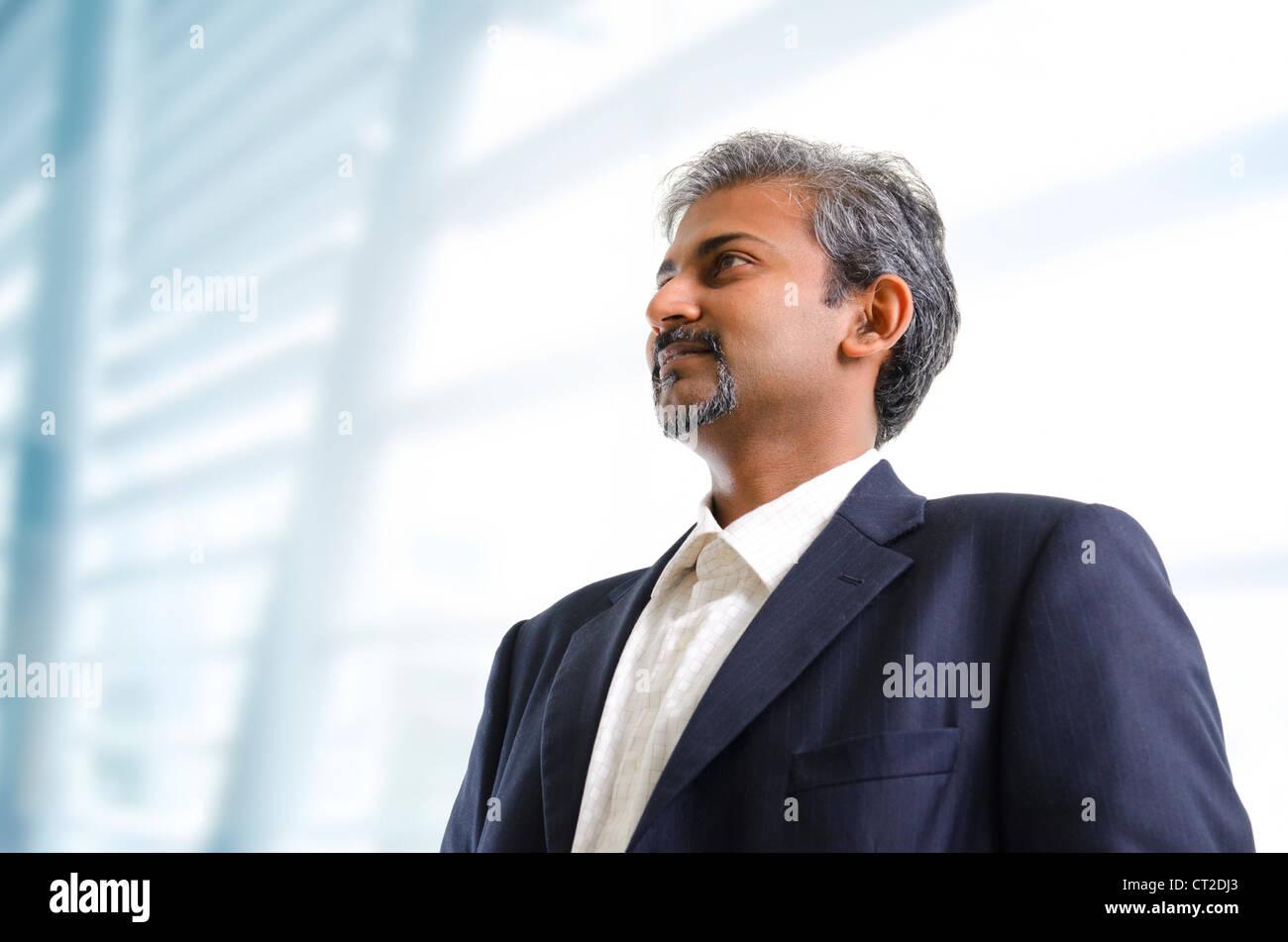 Reife asiatische indische Geschäftsmann aussehende entfernt stehend auf Office-Hintergrund Stockbild