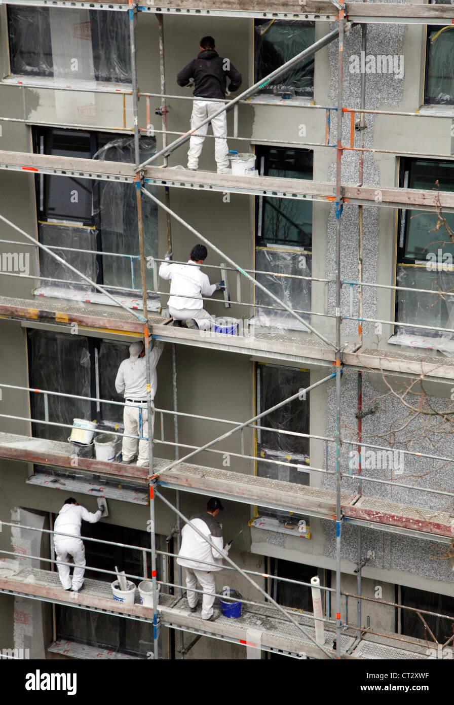 Arbeiter auf einem Gerüst, Isolierung eines Mehrfamilienhauses. Stockbild