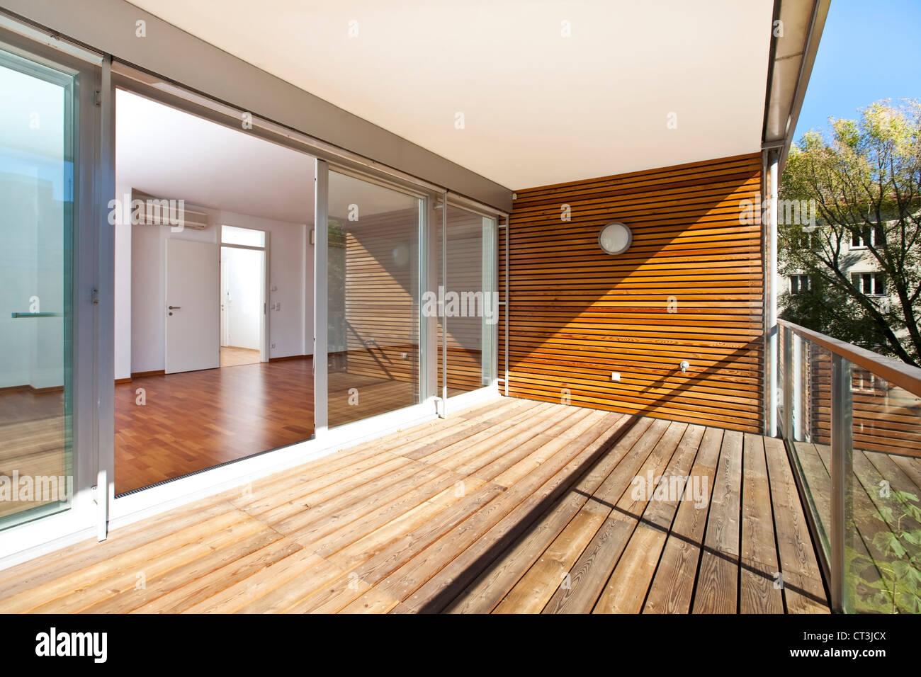 Sonnigen balkon mit holzboden und wand des architektonisch modern