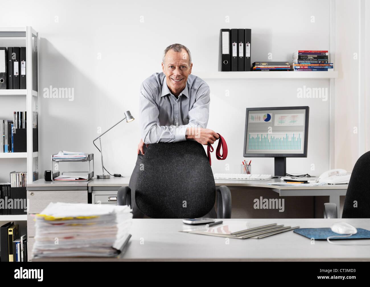 Geschäftsmann, stehend im Büro Stockbild