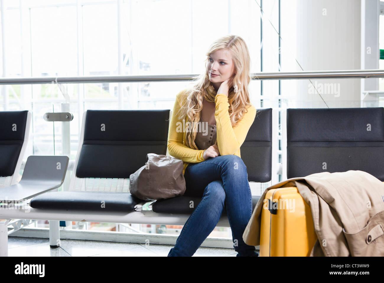 Frau im Wartebereich des Flughafens Stockfoto