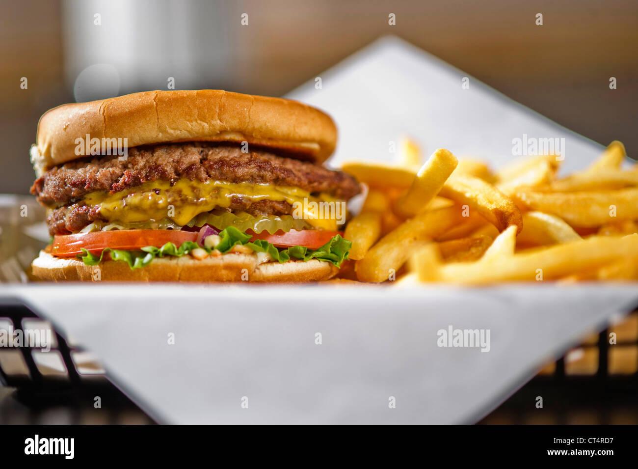 Einen Cheeseburger in einem Korb mit Pommes frites. Stockbild