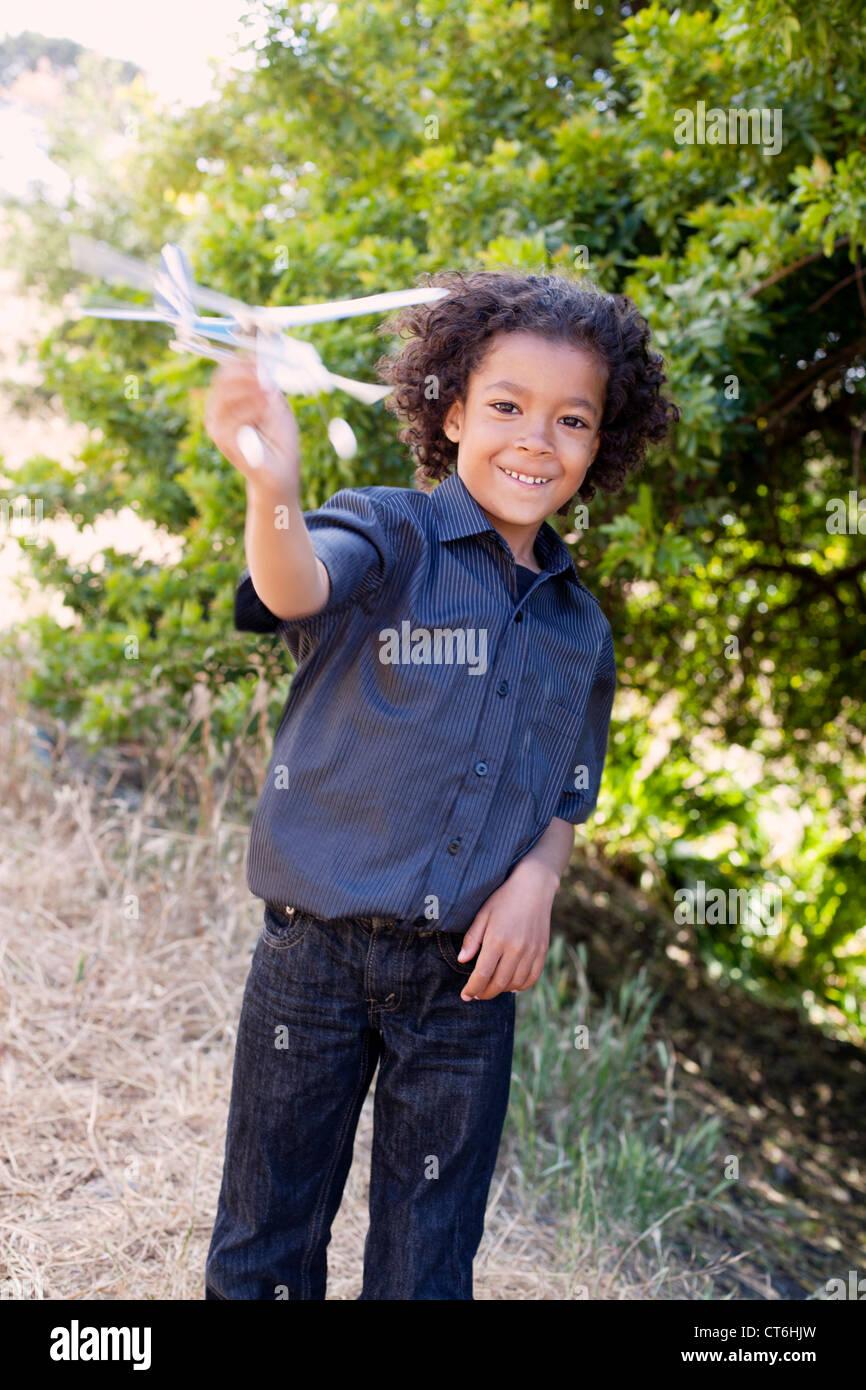 Ein kleiner Junge spielt mit einem Spielzeugflugzeug. Stockbild