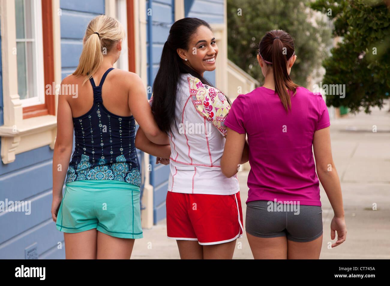 Drei Mädchen in Fitnesskleidung sind Fuß die Straße hinunter. Stockbild