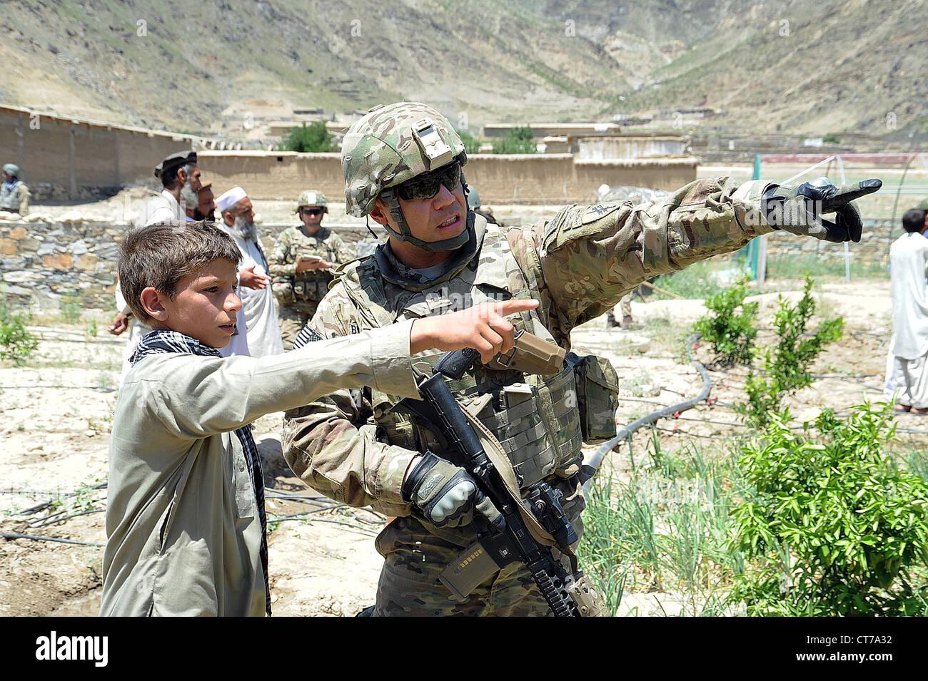 Soldat der US Army spricht zu einem lokalen Teenager über den Standort seiner Schule bei einem Besuch in der Stockbild