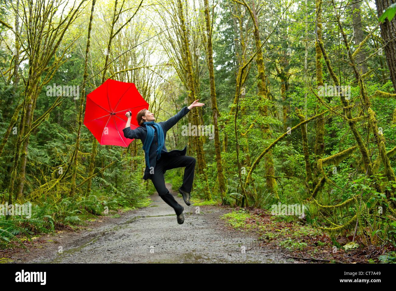 Springende Frau im Wald mit roten Regenschirm Stockbild
