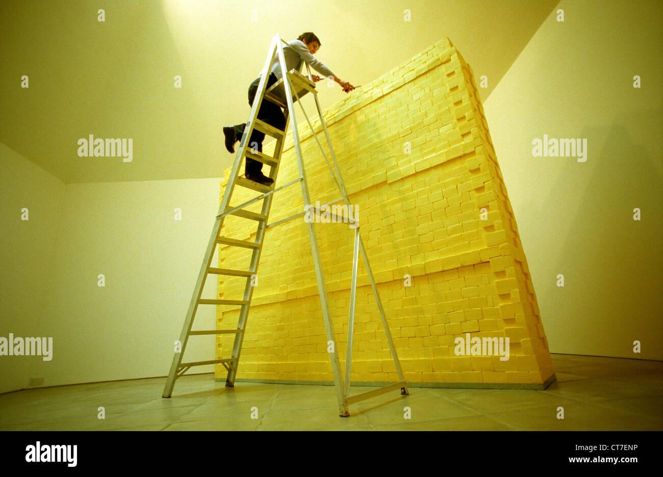 Künstlerin auf Leiter, Bildhauerei eine Wand komplett aus Butter gemacht. Es wog Dreiviertel Tonne und wurde Stockbild