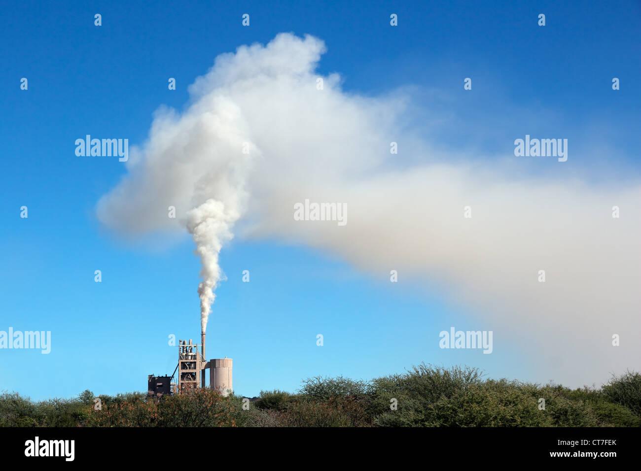 Rauch aus einer Industrieanlage treiben im Wind vor blauem Himmel Stockbild