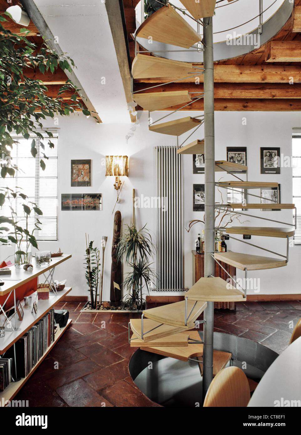 Wendeltreppe in das moderne Wohnzimmer mit Terrakotta-Böden und ...