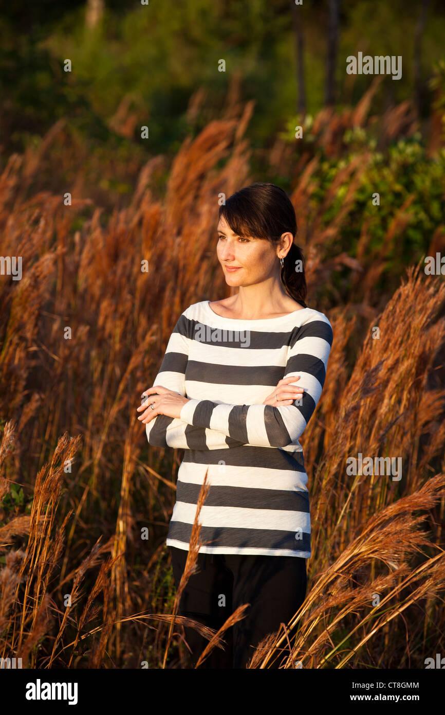 Frau, die Gelenkarme im Feld Stockbild