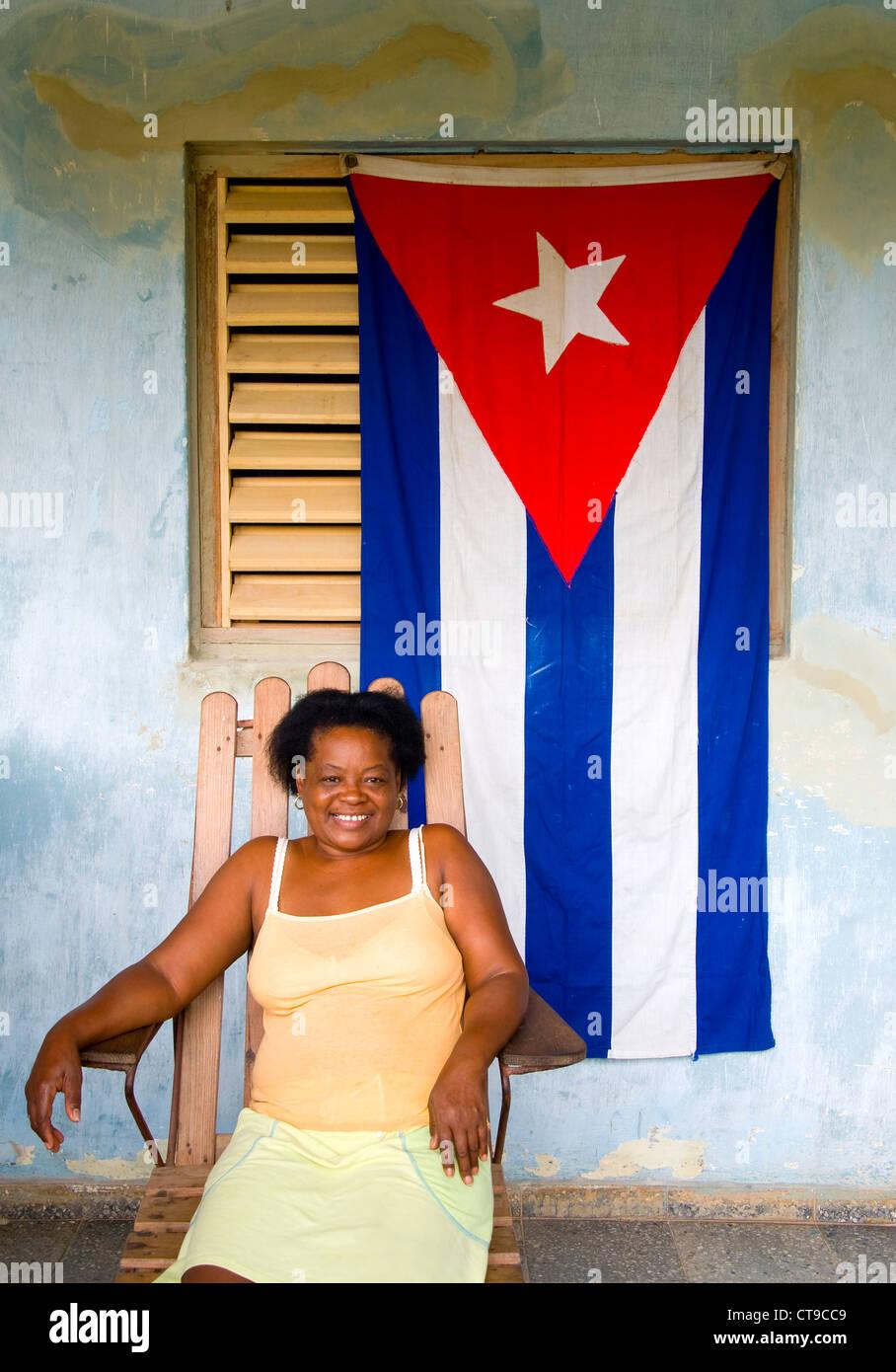 Frau auf der Veranda mit kubanischen Flagge, Viñales, Kuba Stockbild
