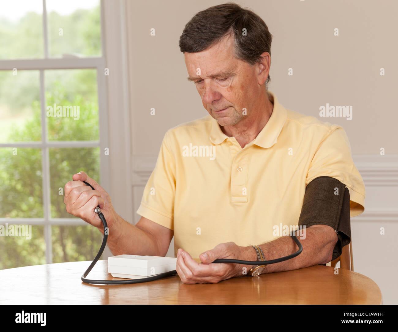 Senior kaukasischen zog sich männliche Einnahme Blutdruck zu Hause Stockbild