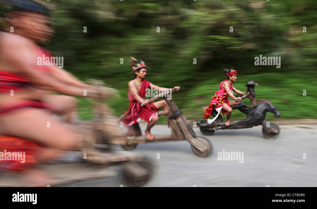 Ifugao Männer Beschleunigung auf hölzernen Roller, Banaue, Ifugao, Insel Luzon, Philippinen Stockbild
