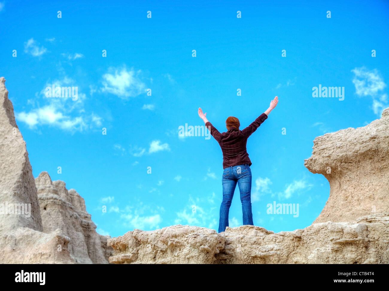 Frau mit erhobenen Händen gegen blauen Himmel Stockbild