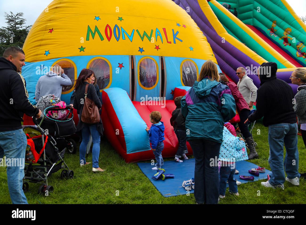 Eltern warten für Kinder, die sind auf Moonwalk Bouncy Castle in Cheam Dorf Fair Surrey England Stockbild