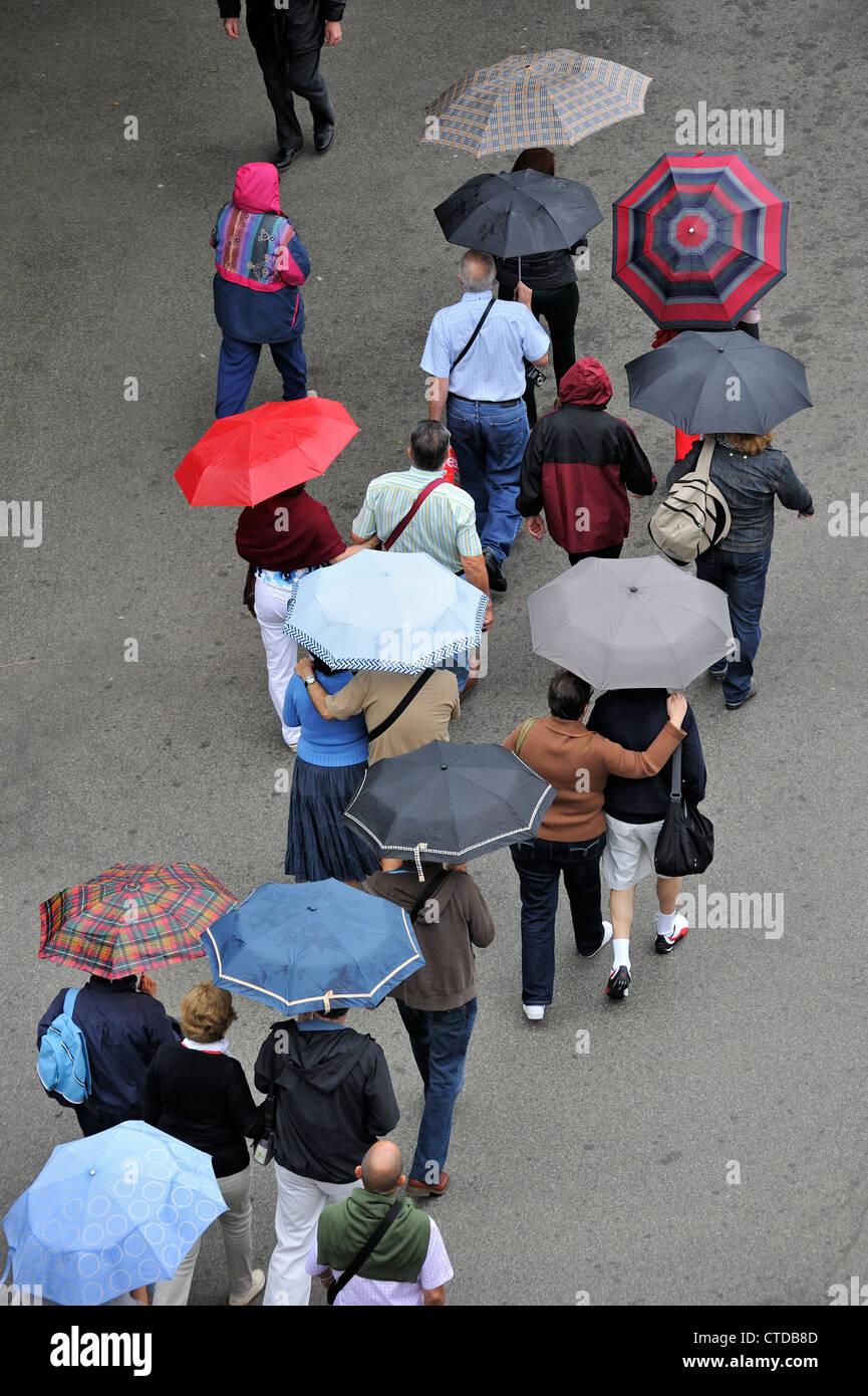 Menschen mit Regenschirmen Wandern in den Regen an einem regnerischen regnerischen Tag im Sommer Stockbild