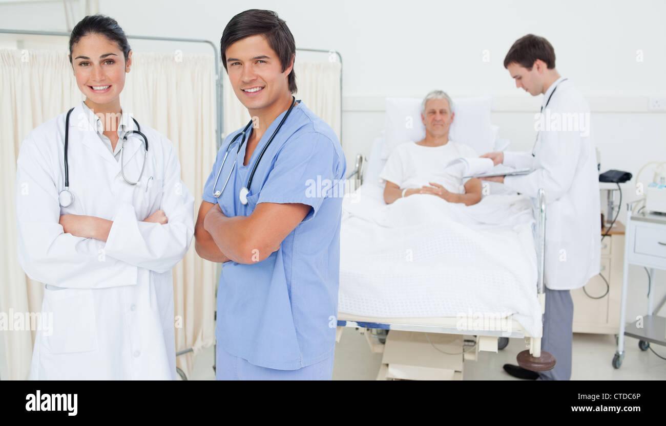 Lächelnd, Arzt und Praktikant beim Falten ihre Arme mit Blick Stockbild