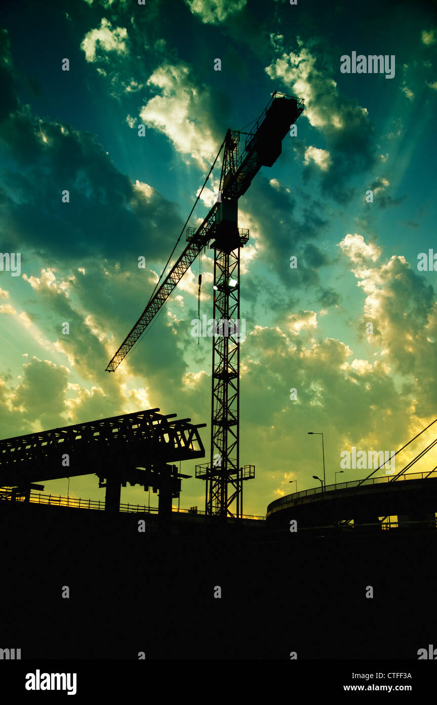 Silhouetten der Baukran und eine Brücke in Dämmerung gegen den bunten Himmel. Stockbild