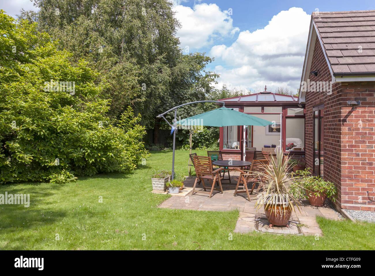 Mittelklasse-Vorort englischer Garten mit Terrasse und Wintergarten. Stockbild