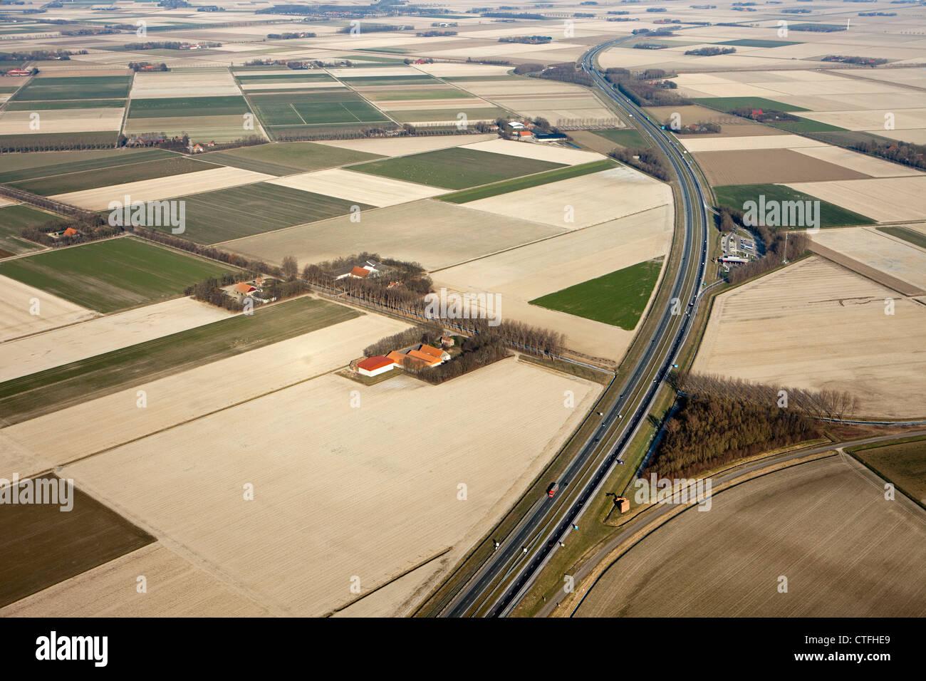 Die Niederlande, Nagele, Farmen und Ackerland in Flevopolder. Auf der Autobahn A6. Antenne. Stockbild