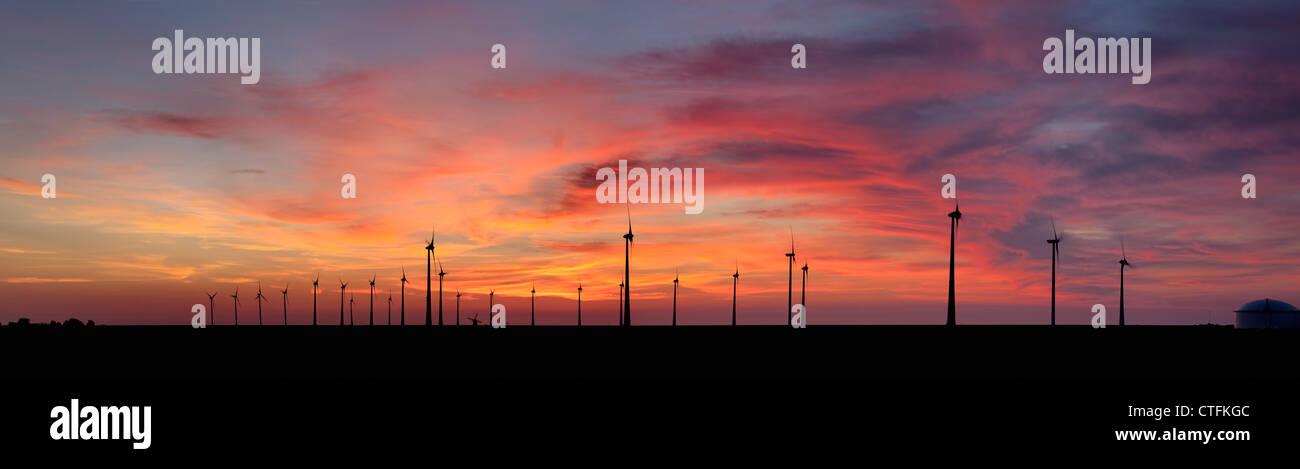 Emsmündung, Eemshaven, Windkraftanlagen und traditionelle Windmühle. Sonnenuntergang. Panorama-Blick. Stockbild
