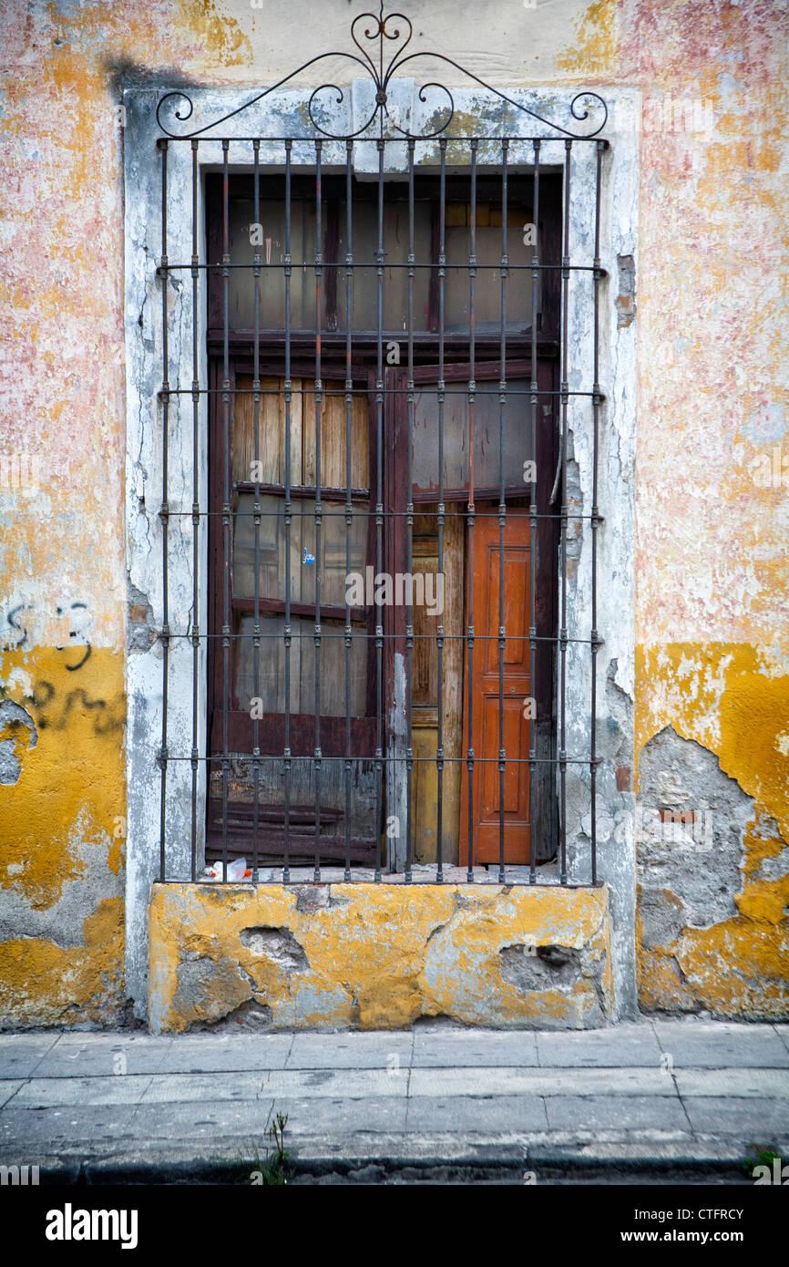 Fenster mit geschlossenem Verschluss und Metallgitter. Stockbild
