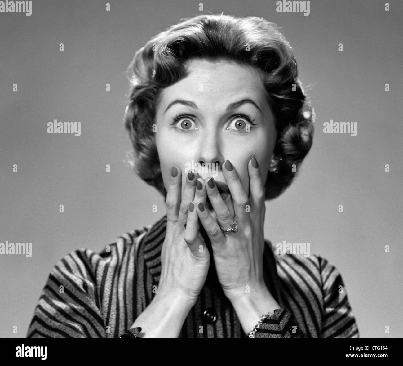 1950ER JAHRE PORTRAIT OF WOMAN IN GESTREIFTEN KLEID HÄNDE IN DEN MUND MIT SCHOCKIERT AUSDRUCK BLICK IN DIE Stockbild
