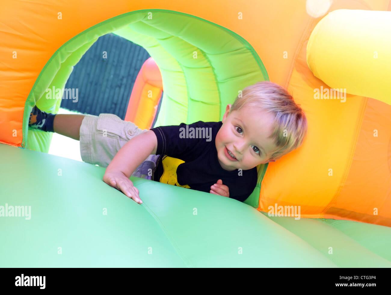 Kind auf Hüpfburg Stockbild