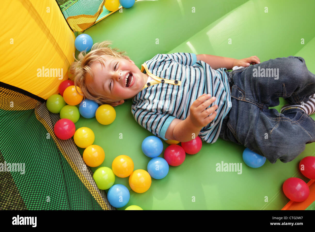 Kind auf aufblasbare Hüpfburg Stockbild