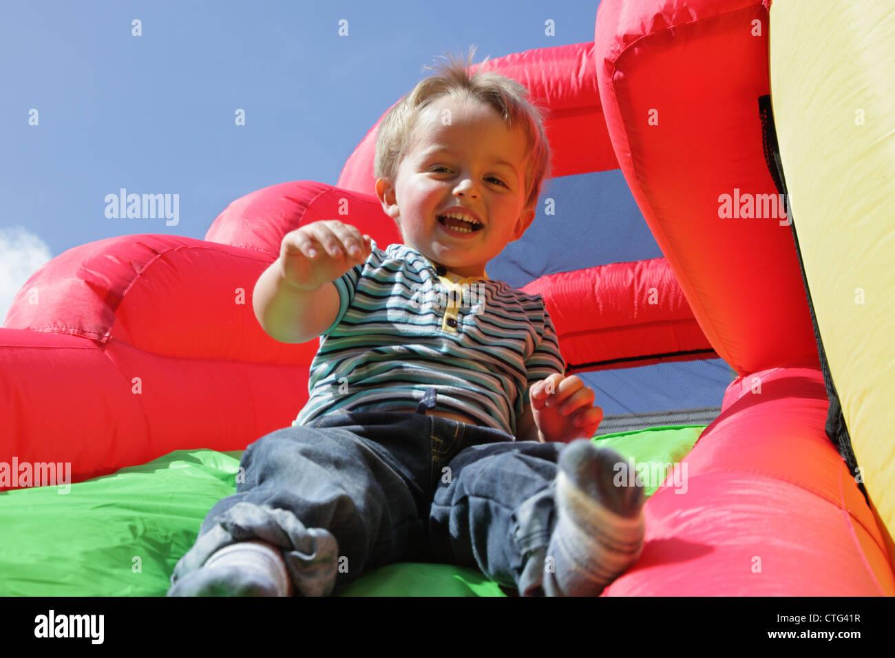 Kind auf aufblasbare Hüpfburg Rutsche Stockbild