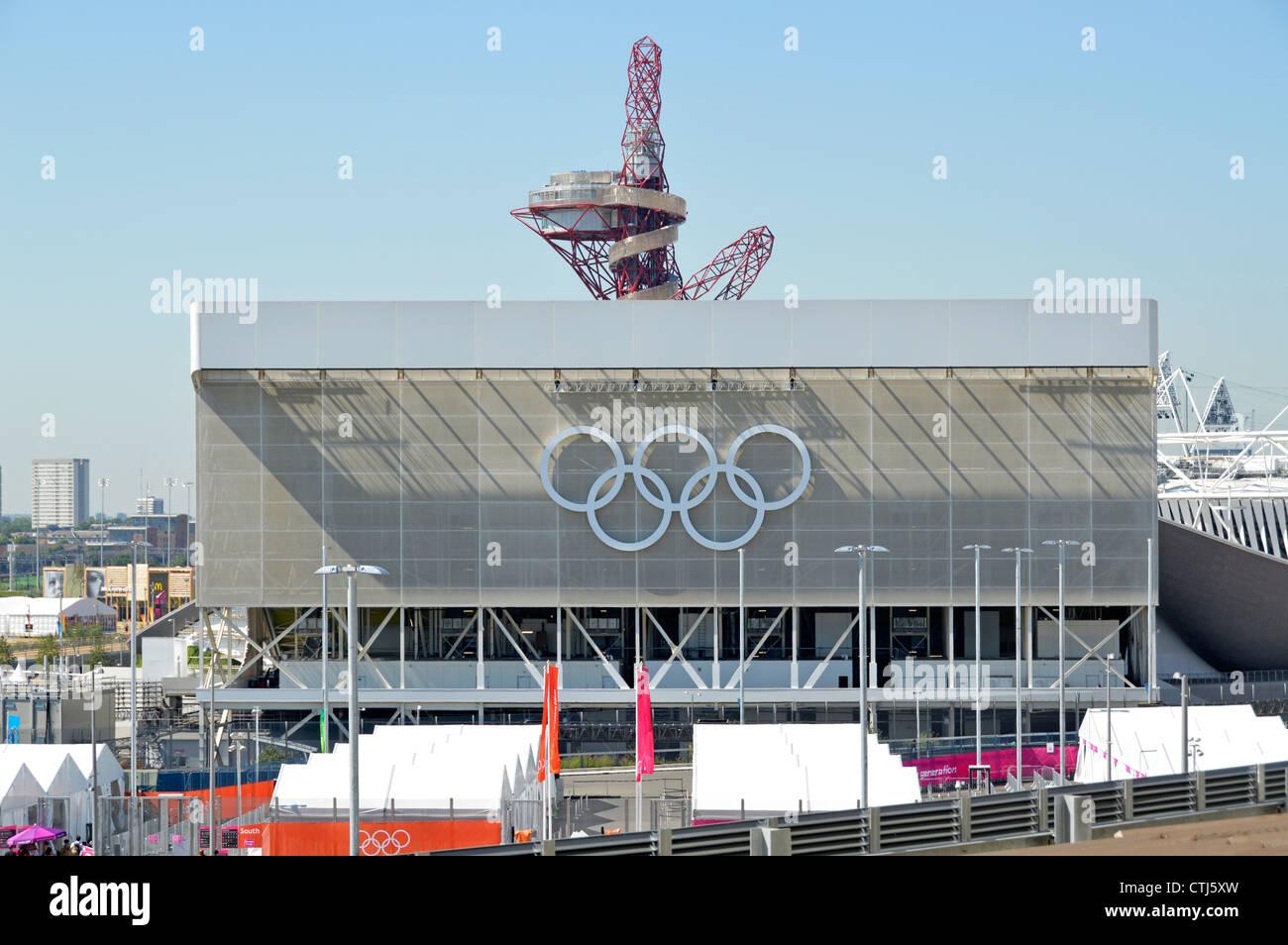 Olympischen Ringe auf die Aquatics Centre mit der ArcelorMittal Orbit Turm über die Olympischen Spiele 2012, Stratford, Stockfoto