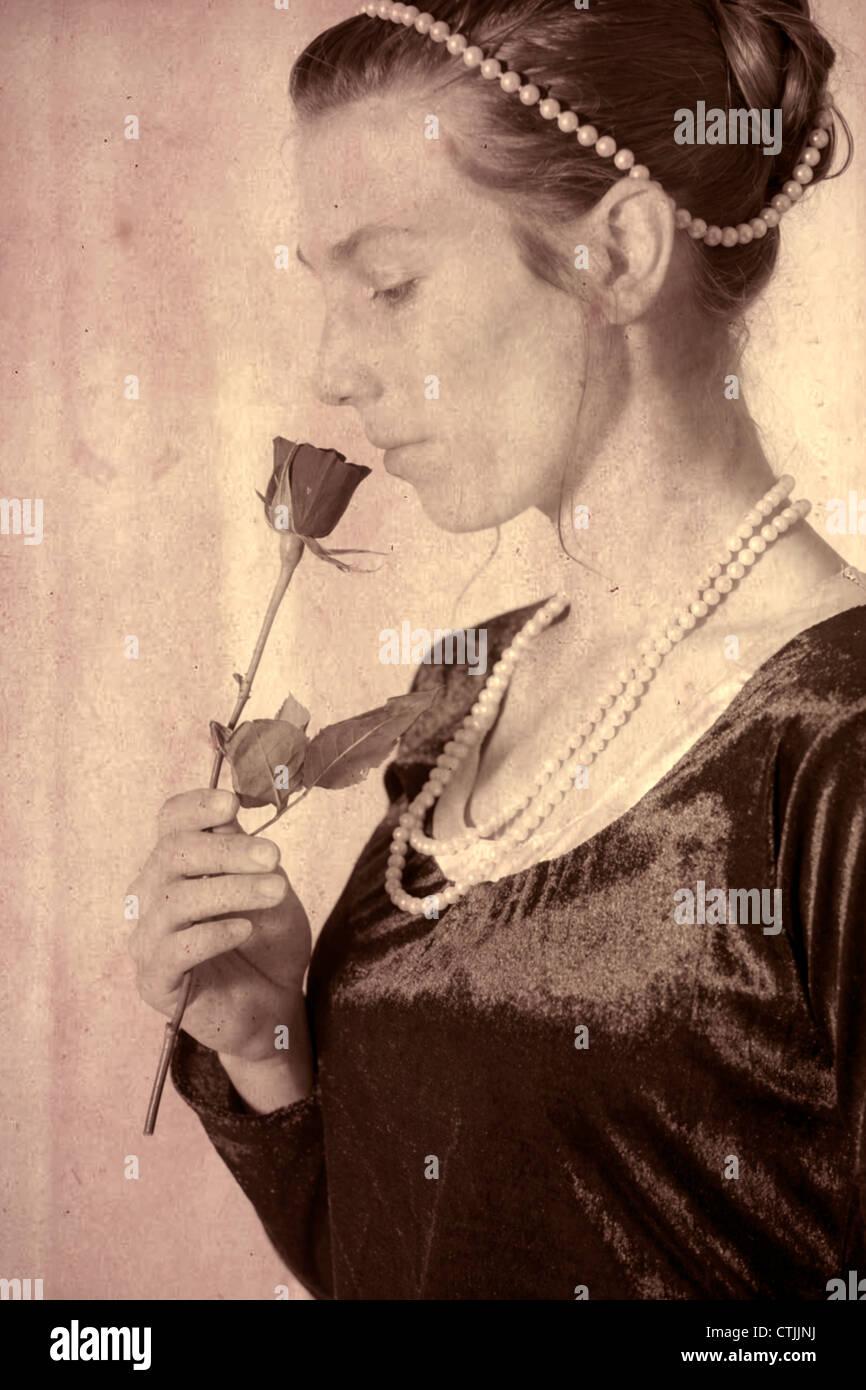 eine elegante Frau eine Rose riecht Stockbild