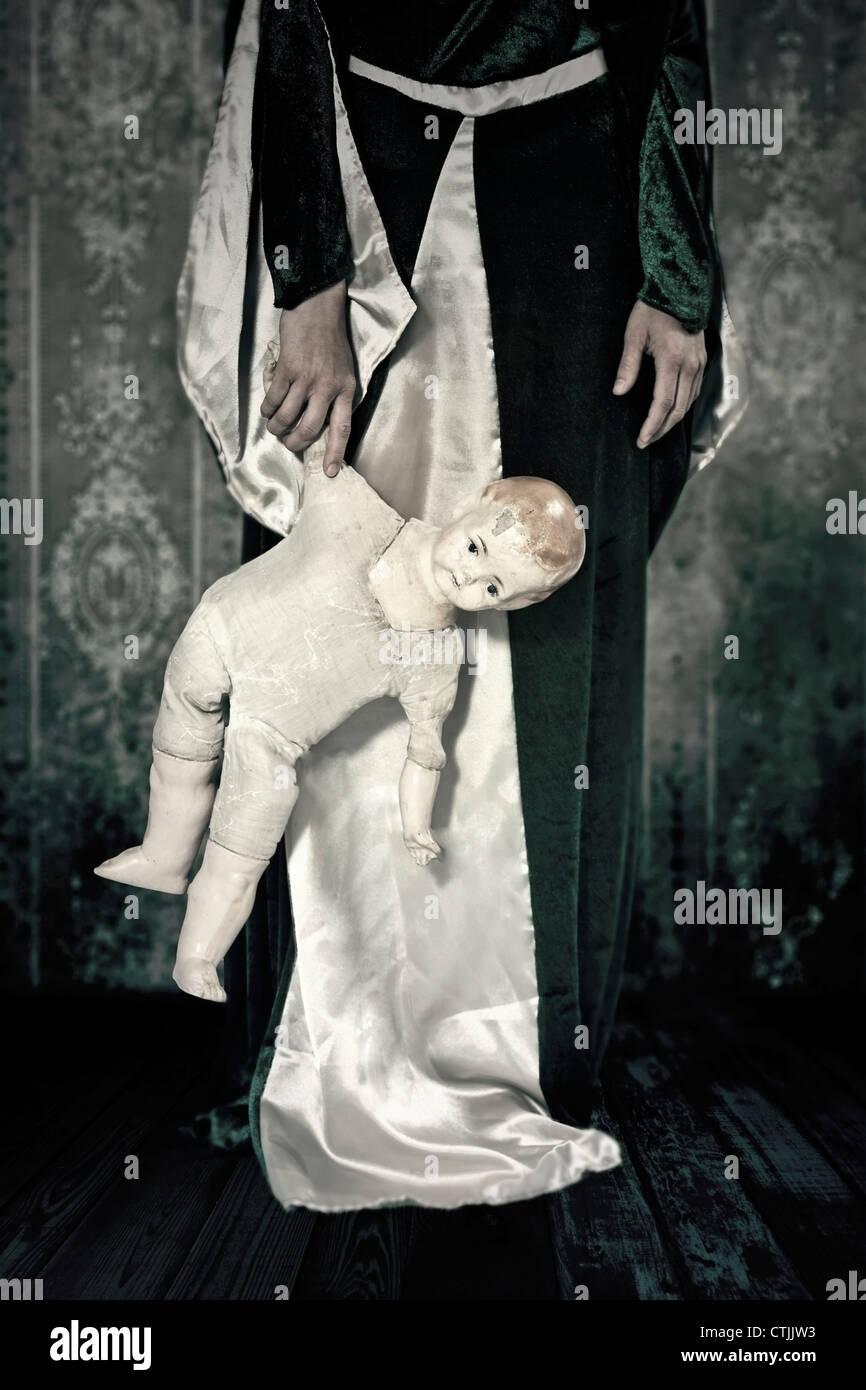 eine Frau in einem Zeitraum Kleid mit einer alten, gebrochenen Puppe in der hand Stockbild